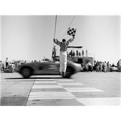Man jumping waving checkered flag